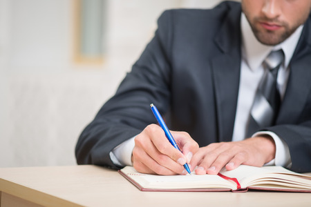 25 30 years: Close-up image of red notebook and hands of businessman sitting at the table in office with a pen attentively writing some notes with copy place Stock Photo