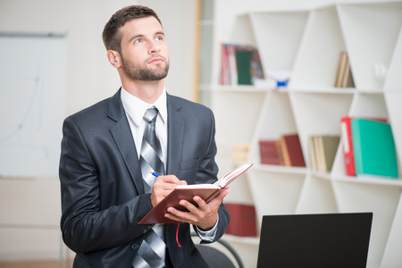 25 30 years: Waist-up portrait of handsome confident businessman sitting at the table and attentively writing some notes in red notebook in office interior and looking up Stock Photo