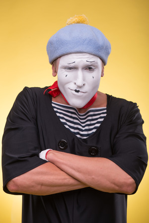 pert: Waist-up portrait of pert mime with white face, grey hat and red scarf playfully looking at the camera folding his hands on his chest isolated on yellow background