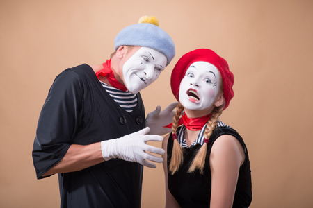 wanting: Close-up horizontal portrait of couple of two funny mimes, male mime wanting to touch and to hug a little scared female mime isolated on beige background with copy place
