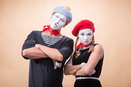 Close-up horizontal portrait of couple of two funny mimes, female mime looking irritating at the camera and male mime looking at his partner isolated on beige background with copy place Stok Fotoğraf