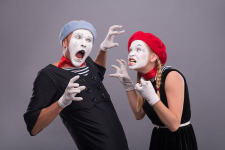 Waist-up horizontal portrait of couple of two mimes standing face to face and screaming on each other and showing horror with their hands isolated on grey background with copy place photo