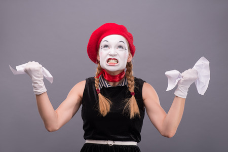 sadistic: Waist-up Portrait of female mime with red hat and white face angry crumpling a paper isolated on grey background with copy place