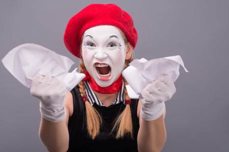 sadistic: Close-up Portrait of female mime with red hat and white face angry crumpling a paper and showing her hands to the camera isolated on grey background with copy place