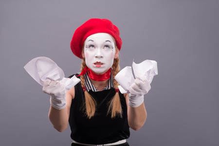 Close-up Portrait of female mime with red hat and white face crumpling a paper and thinking and showing her hands to the camera isolated on grey background with copy place Stock Photo