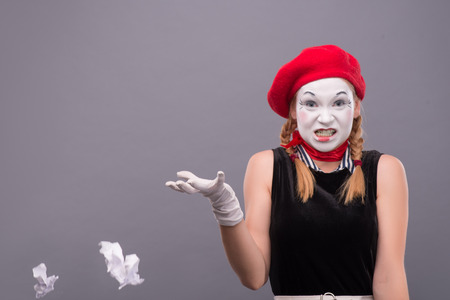 Close-up Portrait of female mime with red hat and white face throwing a crumpled paper and angry looking to the camera isolated on grey background with copy place