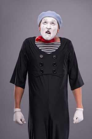 omitted: Waist-up portrait of funny male mime with grey hat and white face disappointed looking up and holding his hands omitted down isolated on grey background with copy place Stock Photo