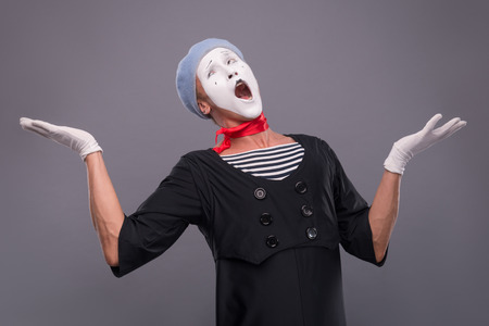 waistup: Waist-up portrait of funny and surprised male mime in red head and with white face with opened mouth looking up and breeding his hands isolated on grey background