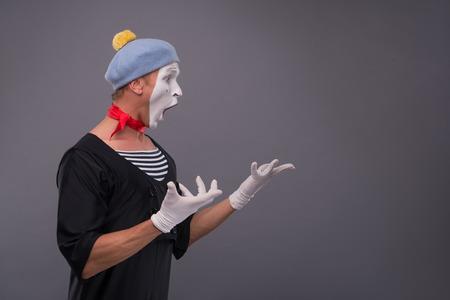 waistup: Retrato Cintura-para arriba del mimo sexo masculino divertido y sorprendido en la cabeza de color rojo y con la cara blanca y la boca abierta mirando a un lado y la cr�a de sus manos aisladas sobre fondo gris con copia lugar