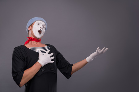 waistup: Waist-up portrait of funny and surprised male mime in red head and with white face and opened mouth looking aside and breeding his hands isolated on grey background with copy place