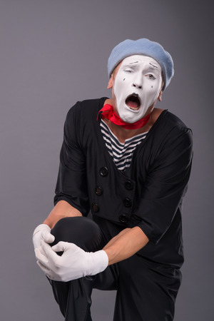 waistup: Waist-up portrait of sad male mime in red head and with white face and opened mouth looking at the camera and holding his leg in his hand isolated on grey background with copy place Stock Photo