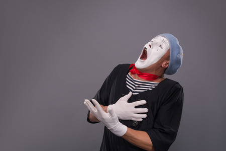 waistup: Waist-up portrait of surprised male mime in red head and with white face and opened mouth looking aside and holding his hands on his chest isolated on grey background with copy place