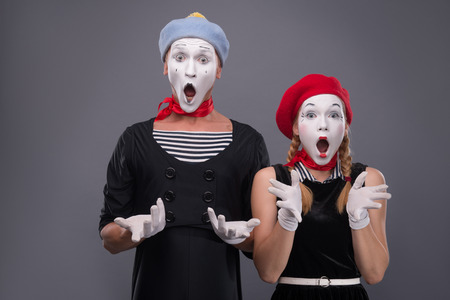 Waist-up portrait of funny mime couple with white faces solemnly singing and waving their hands isolated on grey background with copy place photo