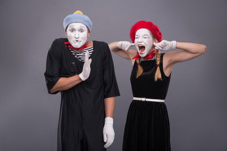 Waist-up portrait of funny mime couple with white faces, female mime closing her ears with her fingers and shouting on male mime carefully waving his hand isolated on grey background photo