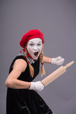 Waist-up portrait of female mime with red hat and white face screaming and holding a rolling pin isolated on grey background with copy place photo
