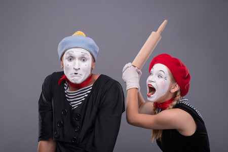 Waist-up portrait of mime couple with white faces, female mime wanting to beat confused male mime with rolling pin isolated on grey background with copy place