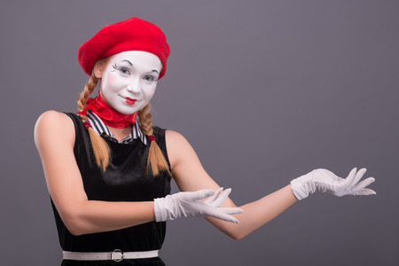 Close-up portrait of female mime with red hat and white face showing with her hands aside and looking at the camera isolated on grey background with copy place photo