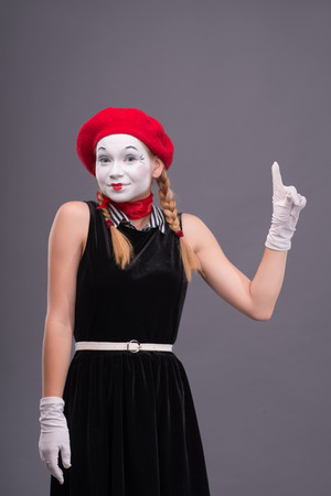 Waist-up portrait of female mime with red hat and white face pretty smiling and looking at the camera and showing sign Attention isolated on grey background with copy place photo
