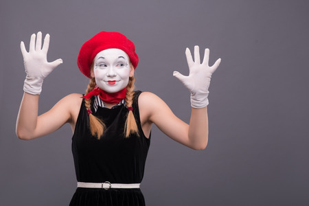 looking aside: Waist-up portrait of female mime with red hat and white face pretty smiling and looking aside and showing her hands isolated on grey background with copy place