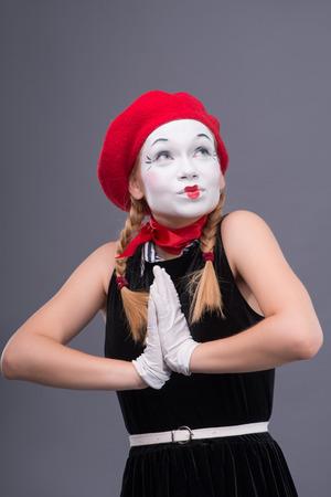 waistup: Retrato Waist-up de mimo de la mujer con el sombrero rojo y blanco rostro muy sonriente y mirando a un lado mientras mantiene sus manos juntas aisladas sobre fondo gris con copia lugar