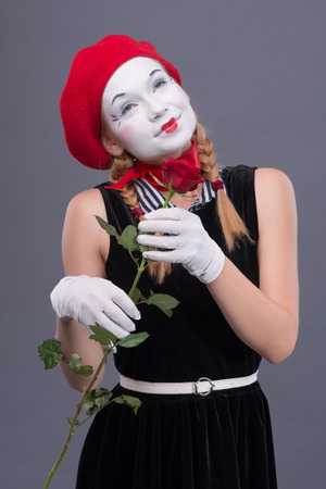 Waist-up portrait of female mime with red hat and white face pretty smiling and looking aside while holding in her hands a rose isolated on grey background with copy place photo