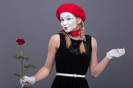 Waist-up portrait of female mime with red hat and white face pretty smiling and looking at the camera while holding in her hands a rose isolated on grey background with copy place photo