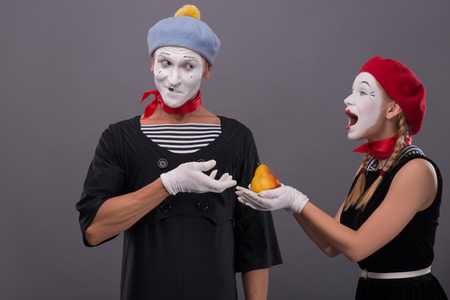 Waist-up portrait of mime couple with white faces, female mime giving a yellow pear to male mime looking on her isolated on grey background with copy place photo