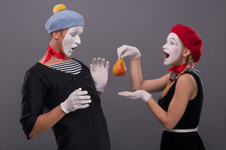 Waist-up portrait of mime couple with white faces, female mime giving a yellow pear to male mime looking on this pear isolated on grey background with copy place photo