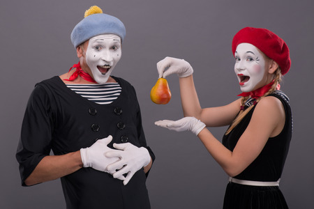Waist-up portrait of mime couple with white faces looking at the camera, female mime giving a yellow pear to male mime isolated on grey background with copy place photo