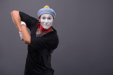 waistup: Retrato Cintura-para arriba del mimo sexo masculino divertido con el sombrero gris y blanco rostro feliz mirando a la c�mara con gran sorpresa y la celebraci�n de sus manos en el pecho aislado en fondo gris con copia lugar