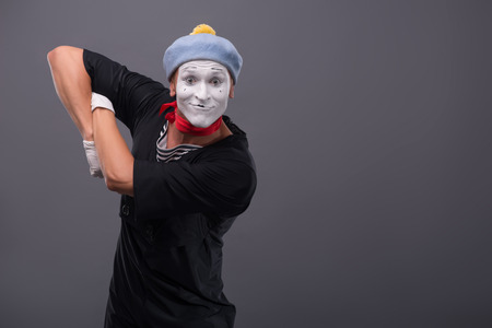 waistup: Waist-up portrait of funny male mime with grey hat and white face happy looking at the camera with great surprise and holding his hands on the chest isolated on grey background with copy place