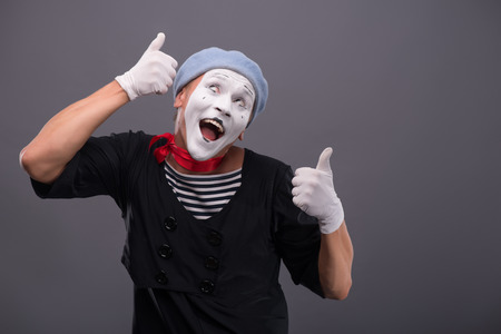 waistup: Waist-up portrait of funny male mime with grey hat and white face showing sign OK with both hands and looking playfully up with happy smile isolated on grey background with copy place