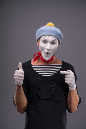 waistup: Retrato Cintura-para arriba del mimo sexo masculino divertido con la cara blanca que muestra con una mano sobre otra se�al que muestra OK y mirando a la c�mara con sonrisa feliz aislado en fondo gris con copia lugar Foto de archivo