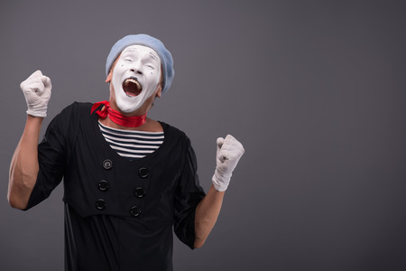 waistup: Waist-up portrait of funny male mime with grey hat and white face showing sign YES with both hands and closing his eyes and smiling isolated on grey background with copy place