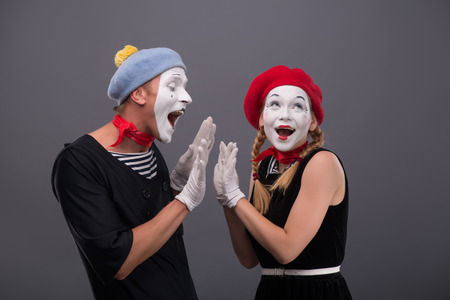 clasping: Waist up portrait of mime couple with white faces clasping each other hands,  female mime looking aside, male mime lovely smiling isolated on grey background with copy place
