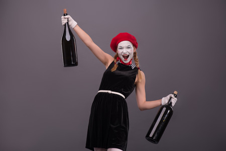 Waist-up Portrait of young drunk mime girl holding big bottles in her hands well smiling and looking at the camera isolated on grey background with copy place photo