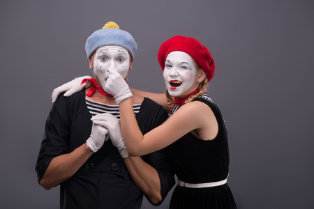 Waist-up portrait of funny mime couple looking at the camera, male mime holding his hands on the chest, female mime touching his nose isolated on grey background with copy place photo