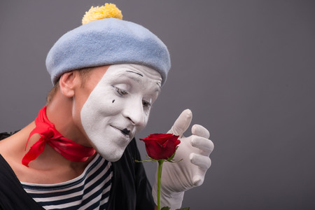 Close-up side-view portrait of young male mime with white face and grey hat holding a red rose and amazed looking at this flower isolated on grey background with copy place