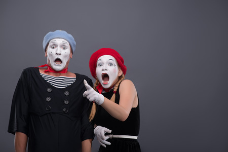 Waist-up portrait of scared mime couple looking at the camera, female mime loudly crying and showing at you standing near male mime with startled face isolated on grey background with copy place Banco de Imagens