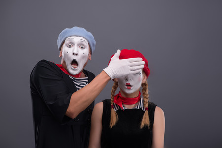 consternation: Waist-up portrait of scared mime couple, male mime looking at the camera with consternation on his face and closing eyes of his girlfriend isolated on grey background with copy place Stock Photo