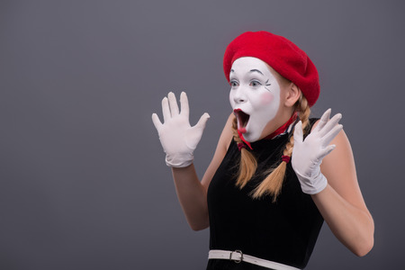 mimic: Waist-up portrait of young mime girl with red hat and red scarf looking aside with pleasant surprise, showing that she is happy to see something, isolated on grey background with copy place Stock Photo