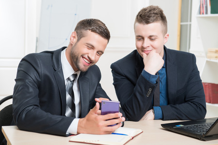 waistup: Waist-up portrait of two handsome businessmen in suits sitting at the table in office interior, one holding in his hands a mobile phone and both lightly laughing while looking on the screen of phone