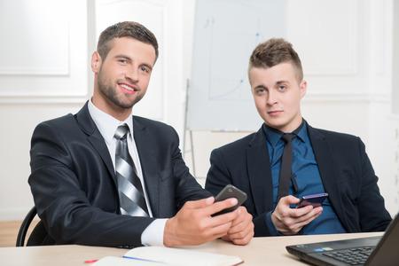 waistup: Cintura-up retrato de dos hombres de negocios guapo en traje sentado en la mesa y sosteniendo en sus manos los tel�fonos m�viles y mirando a la c�mara con una bonita sonrisa en el interior de oficinas Foto de archivo