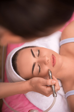 Close-up top-view portrait of a young woman with a towel on her head lying on a table with closed eyes getting a laser skin treatment in healthy beauty spa salon