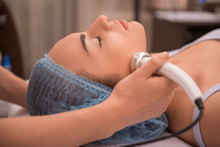 Close-up portrait of a young woman with a towel on her head lying on a table with closed eyes getting a laser skin treatment in healthy beauty spa salon photo