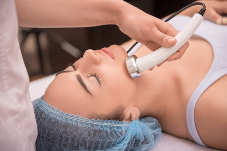 dermatology: Close-up top-view side-view portrait of a young woman with a towel on her head lying on a table with closed eyes getting a laser skin treatment in healthy beauty spa salon Stock Photo