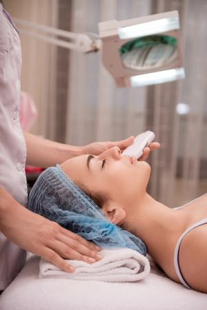 manipulate: Side-view portrait of a young woman with fresh and clean skin closing her eyes and lying on a table getting a professional cosmetology procedures in healthy beauty spa salon