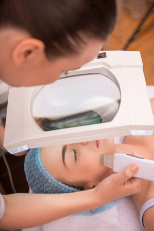eyes closing: Top-view portrait of a young woman with fresh and clean skin closing her eyes and lying on a table getting a professional cosmetology procedures in healthy beauty spa salon Stock Photo