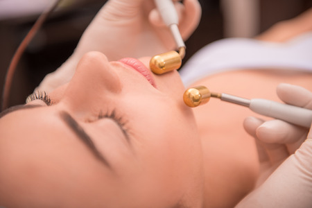 specialized: Close-up portrait of face of a young woman with fresh and clean skin lying on a table in healthy beauty spa salon getting a professional cosmetology skin care with specialized equipment