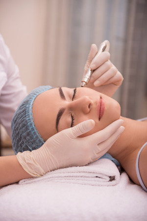 specialized: Side-view portrait of face of a young woman with fresh and clean skin lying on a table in healthy beauty spa salon getting a professional cosmetology skin care with specialized equipment